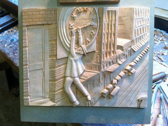 A wooden carving of a famous Harold Lloyd scene